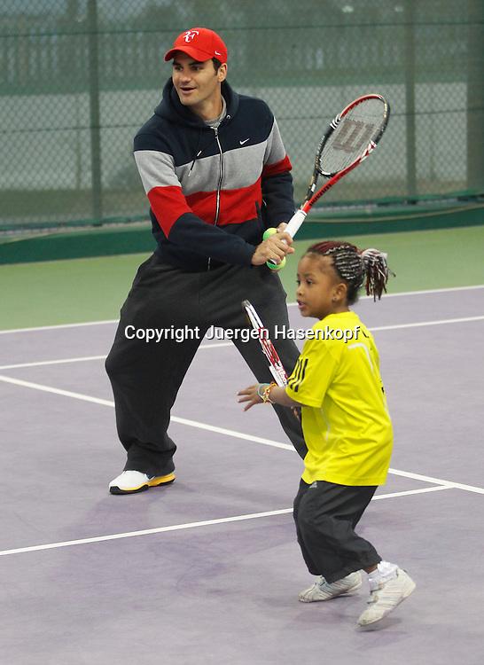 Qatar ExxonMobil Open2011, ATP TennisTurnier, International Series, Khalifa International Tennis & Squash Complex,Doha,Qatar, Roger Federer (SUI) spielt Tennis mit Kindern, hier die acht Jahre alte Dana waehrend der Kid's Clinic,
