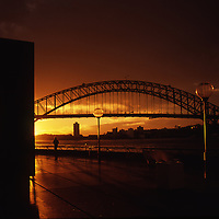 Setting sun silhouettes Sydney Harbor Bridge. View from Opera House forecourt. Small human sihouette faces sunset.