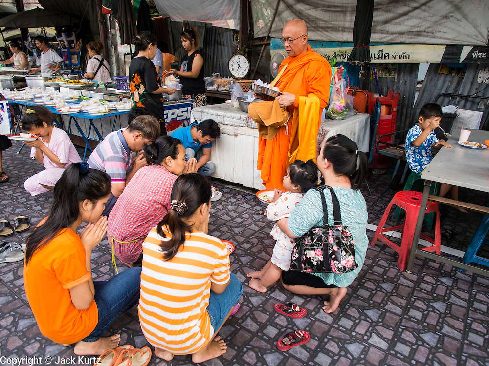 20 JUNE 2014 - BANGKOK, THAILAND: Thais kneel and pray in Wong Wian Yai train station after presenting alms to a Buddhist monk. The monk then prayed for them.   PHOTO BY JACK KURTZ