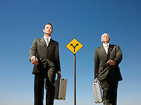 Two businessmen walking past road sign