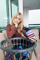 Tired woman with laundry basket sitting on sofa at home