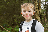 Young boy playing/exploring woodland as part of forest kindergarten session, Mucky Boots, Aberdeen Scotland.<br /> MR available