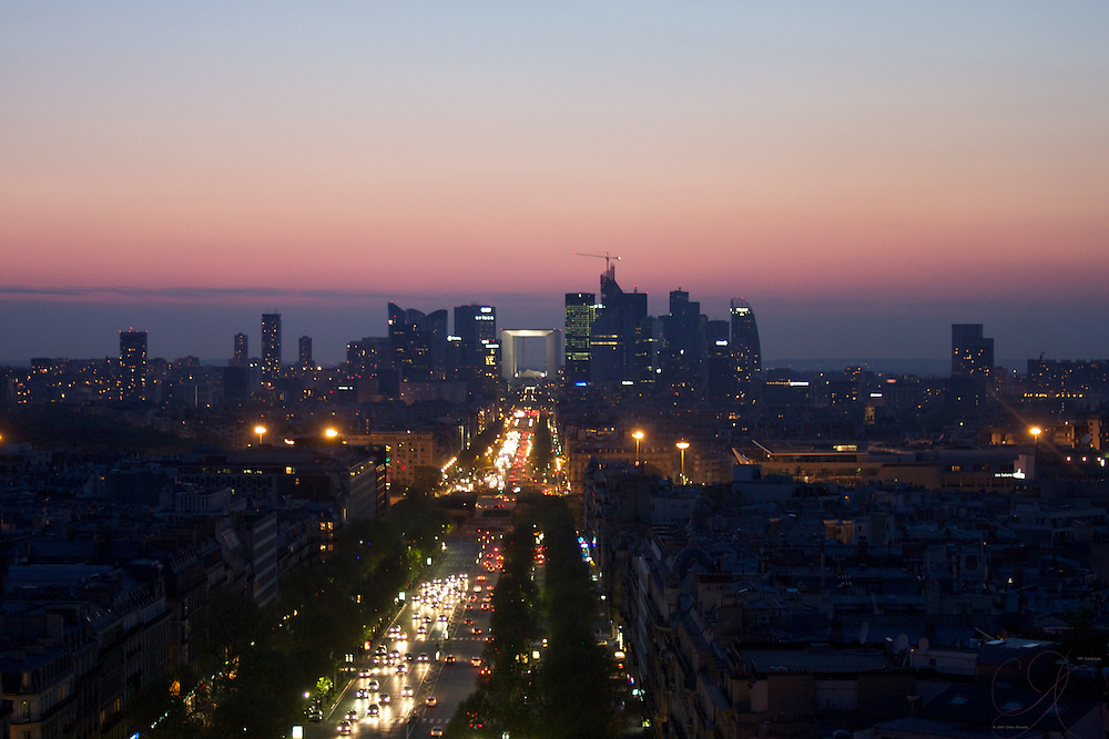From the top of the Arc de Trumphe at sunset, looking at the La Defense skyline of Paris, as the Champs Elyesses flows right to it.