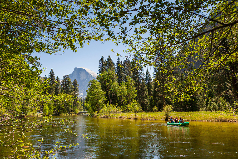 Tourists rafting the Merced River in Yosemite National Park with a view of Half Dome.