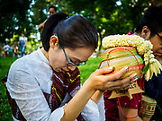 "17 MARCH 2018 - BANGKOK, THAILAND:  A woman prays before presenting cooked sticky rice to monks during a ""sticky rice merit making"" in Lumpini Park in Bangkok. Sticky rice merit making is a merit making in the Isan / Lao style, when people present small amounts of cooked sticky rice (also known as glutinous rice) to Buddhist monks. Isan is the northeast region of Thailand.   PHOTO BY JACK KURTZ"