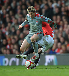 Fernando Torres of Liverpool takes on Patrice Evra of Manchester United during the Barclays Premier League match between Manchester United and Liverpool at Old Trafford on March 14, 2009 in Manchester, England.