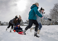 © Licensed to London News Pictures. 27/02/2018. Bearsted, UK. Children pull their sledges across the green in Bearsted, Kent after school was closed due to heavy snow. Freezing temperatures and heavy snow are affecting large parts of Kent.  Photo credit: Peter Macdiarmid/LNP