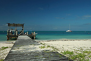 Dock, beach, and sea on tiny barrier island in Belize.