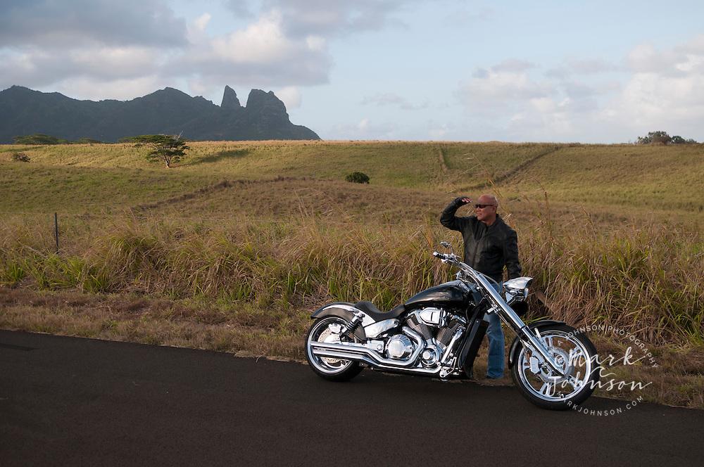 Hawaiian man posing by road motorcycle, Kauai, Hawaii