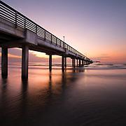 Sun is rising over Texas Coast with a view of Horace Caldwell Pier, Port Aransas, Texas.
