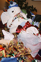 Christmas morning leaves the wrap all over the floor and the ribbons in a heap on a teddy bear.