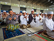 16 JUNE 2015 - CHANAE, NARATHIWAT, THAILAND:  Thai Muslim men participate in a prayer service in Chanae. About 600 people from Muslim communities in Chanae district of Narathiwat province came to the district offices Tuesday morning to participate in a prayer for peace during Ramadan. About 6,000 people have been killed in sectarian violence in Thailand's three southern provinces of Narathiwat, Pattani and Yala since a Muslim insurgency started in 2004. Attacks usually spike during religious holidays. Insurgents are fighting for more autonomy from the central government in Bangkok.       PHOTO BY JACK KURTZ