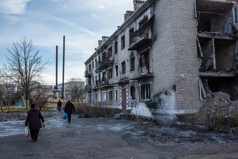 Local residents walk past a destroyed building after receiving free bread delivered by the Good Word Protestant Church in need on Thursday, December 10, 2015 in Mariinka, Ukraine.
