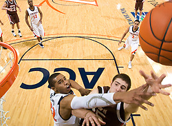 Virginia forward Mike Scott (32) disrupts a shot by Brown forward Matt Mullery (45).  The Virginia Cavaliers defeated the Brown University Bears 74-50 in NCAA Basketball at the John Paul Jones Arena on the Grounds of the University of Virginia in Charlottesville, VA on January 6, 2009.