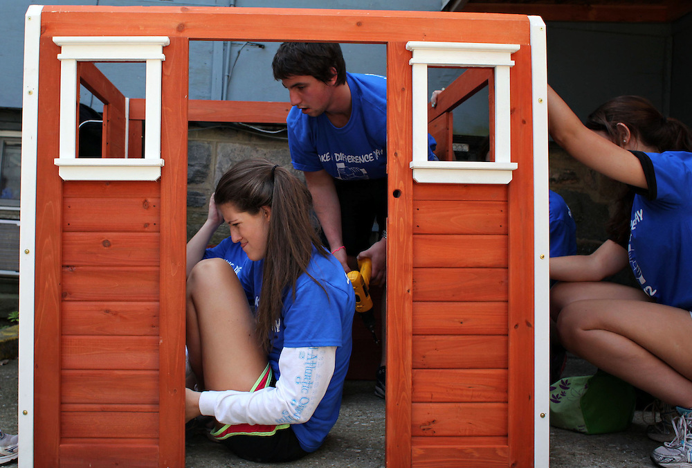 "Xavier Mascareñas/The Journal News; Ursuline student Daniela Leuthold of Rye, 18, center, sits in a playhouse she is helping to construct during ""Make A Difference Day"" at SAIL at Ferncliff Manor, a school for people with developmental disabilities, in Yonkers on April 21, 2012. Students performed community service at various New Rochelle and Yonkers sites throughout the day, representing the New Rochelle Roman Catholic high schools of Blessed Sacrament-St. Gabriel High School, Iona Preparatory School, Salesian High School and The Ursuline School."