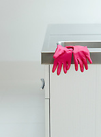 Pink rubber gloves on edge of sink
