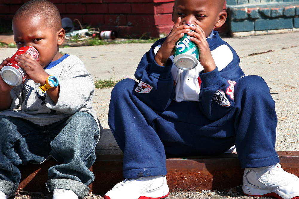 February 28th 2006. New Orleans, Louisiana. United States..Two boys drink their soda after the Zulu Mardi gras Walking Parade on Orleans Avenue.