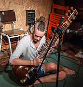 Young Caucasian musician plays a Sitar