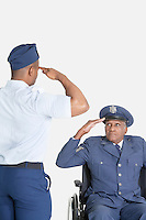 Male cadet saluting senior air force office in wheelchair over light gray background