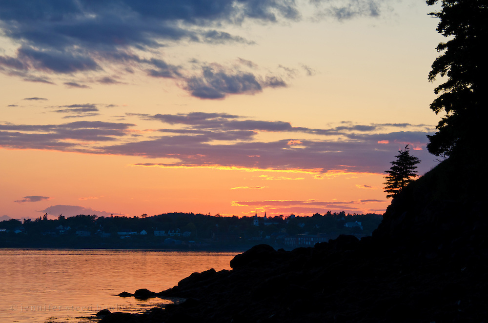 Sunset with gilt-edged clouds and silhouetted spruce trees, from Campobello Island, Canada looking across at Eastport, Maine.