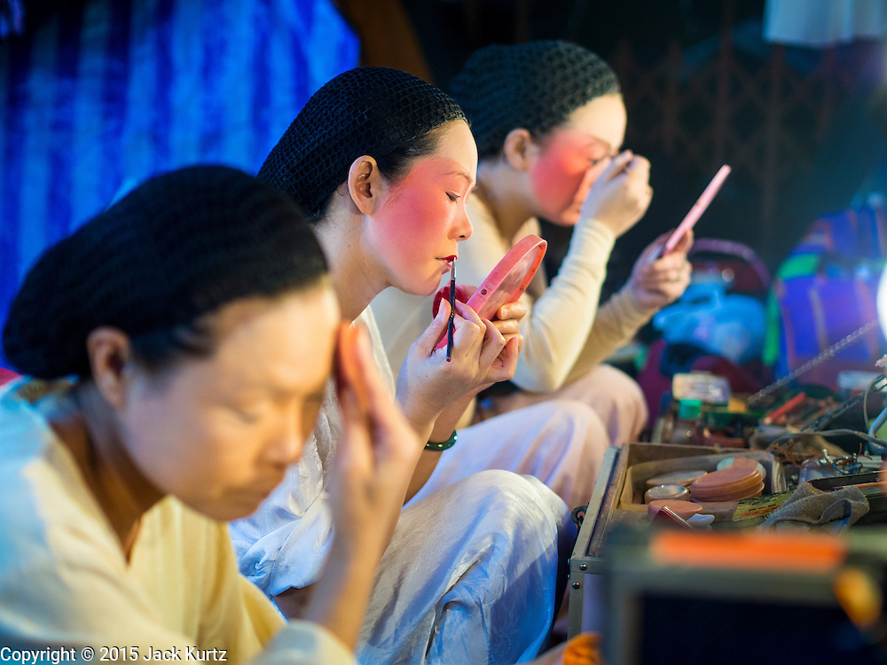 16 JANUARY 2015 - BANGKOK, THAILAND: Performers with the Sai Yong Hong Teochew Opera Troupe put on their make up before performing at the Chaomae Thapthim Shrine, a Chinese shrine in a working class neighborhood of Bangkok near the Chulalongkorn University campus. The troupe's nine night performance at the shrine is an annual tradition and is the start of the Lunar New Year celebrations in the neighborhood. Lunar New Year, also called Chinese New Year, is officially February 19 this year. Teochew opera is a form of Chinese opera that is popular in Thailand and Malaysia.    PHOTO BY JACK KURTZ