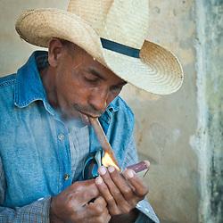 Young man with straw hat lighting a cigar, Trinidad, Sancti Spiritus, Cuba, Caribbean