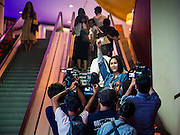 20 NOVEMBER 2014 - BANGKOK, THAILAND:  NATCHACAH KONG-UDOM holds up her movie ticket to the Hunger Games while riding the escalator to the theater at the Siam Paragon movie theaters. She was one of at least three people arrested by Thai police during the opening the Hunger Games: Mockingjay - Part 1 in Bangkok Thursday. Opponents of the Thai military coup have adapted the three fingered salute used in the Hunger Games series as a sign of their opposition to the coup. In the weeks before the movie opening Thai police arrested several people for using the Hunger Games salute and Thai media reported that one Thai movie theater chain cancelled plans to show the movie at the request of the military government. There were several small protests at theaters showing the movie Thursday.    PHOTO BY JACK KURTZ