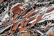 Corregated roof debris. Independence Mine State Historic Park, 14 miles from Palmer, Alaska, USA. The Independence Mines were a gold mining operation in the Talkeetna Mountains, across Hatcher Pass from Palmer. Independence Mine was the second-largest hard-rock gold mining operation in Alaska, after a larger site near Juneau. Mining here dates back to 1897 around Fishook Creek; these claims joined to form Wasilla Mining Company, which worked the mines from 1934-1943 and again 1948-1950. The company ended operations in 1950 expecting to resume, but never did, thereby well-preserving its mining equipment and buildings for eventual donation to the state in 1980, which established Independence Mine State Historic Park.