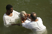 Baptising at the Jordan River, Israel. At the place, that according to legend, John the Baptist, baptised Jesus Christ