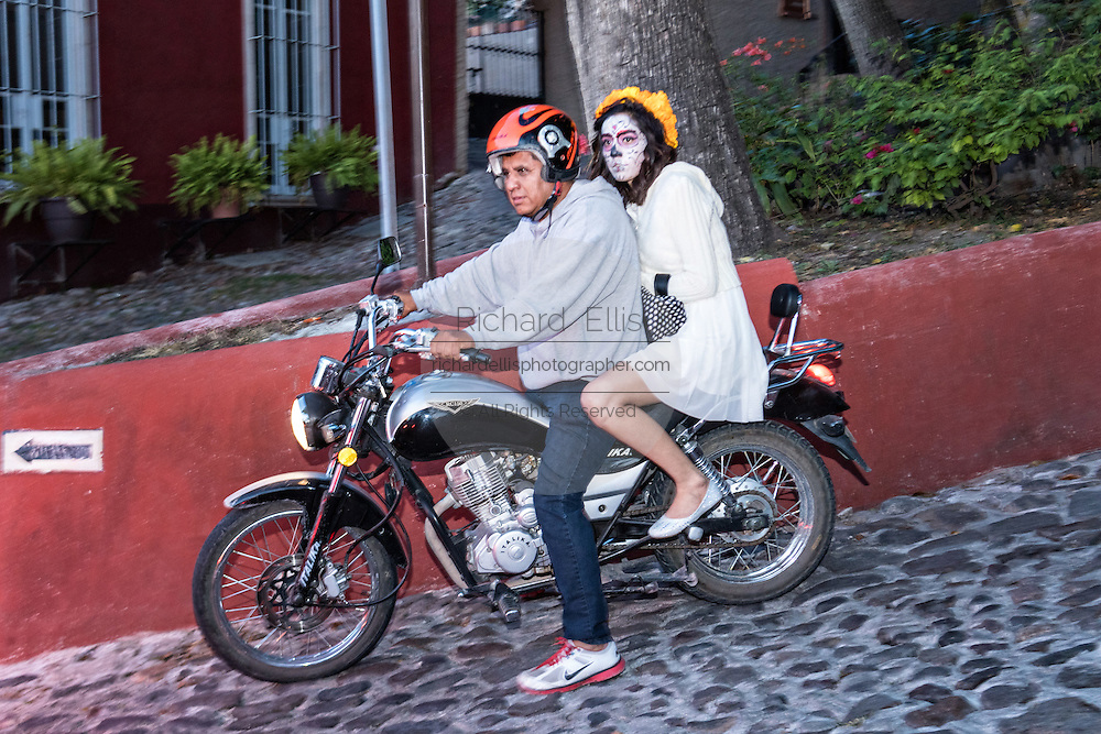 A young woman dressed as La Calavera Catrina rides on the back of a motorcycle during the final day of the Day of the Dead festival November 2, 2016 in San Miguel de Allende, Guanajuato, Mexico. The week-long celebration is a time when Mexicans welcome the dead back to earth for a visit and celebrate life.