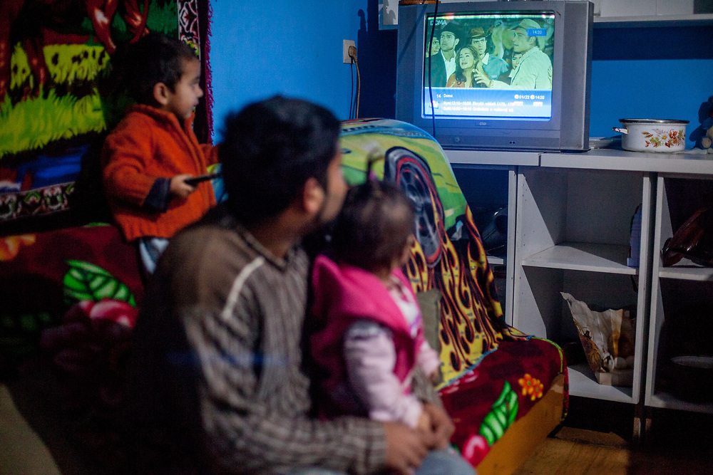 Michal (22) watching television in the new house of his friend Emil in Rankovce where the foundation ETP Slovakia has a project setting up micro-loan funds for the local Roma community. Loans from this fund will enable families to build their own low-cost brick homes, on land they own.