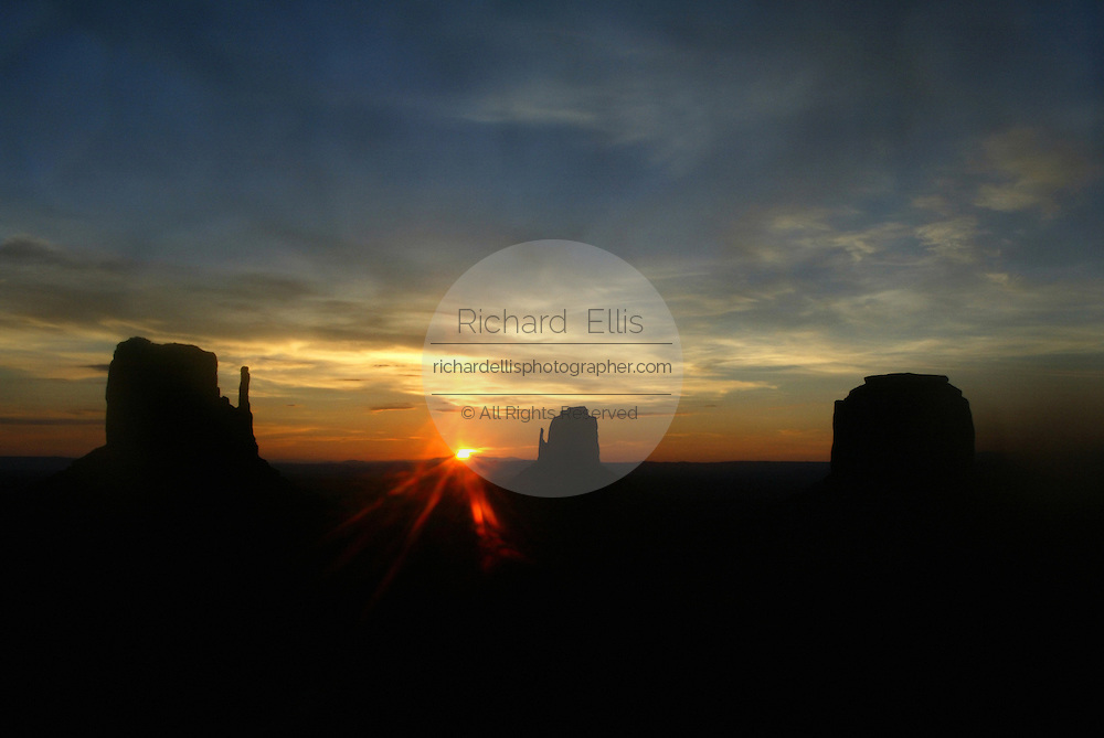 Sunset over the Mittens in Monument Valley on the southern border of Utah with northern Arizona. The valley lies within the range of the Navajo Nation Reservation. The Navajo name for the valley is Tsé Bii' Ndzisgaii - Valley of the Rocks.