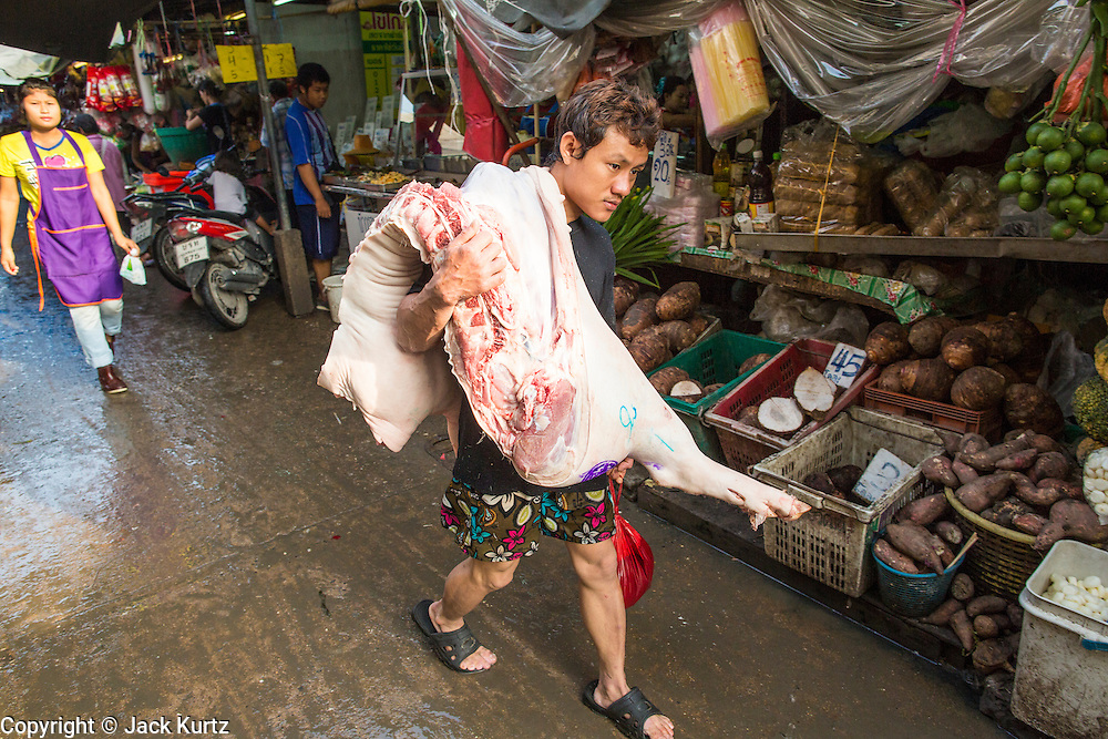 """26 SEPTEMBER 2012 - BANGKOK, THAILAND:   A man delivers sides of pork to a butcher shop in Khlong Toey Market in Bangkok. Khlong Toey (also called Khlong Toei) Market is one of the largest """"wet markets"""" in Thailand. The market is located in the midst of one of Bangkok's largest slum areas and close to the city's original deep water port. Thousands of people live in the neighboring slum area. Thousands more shop in the sprawling market for fresh fruits and vegetables as well meat, fish and poultry.   PHOTO BY JACK KURTZ"""