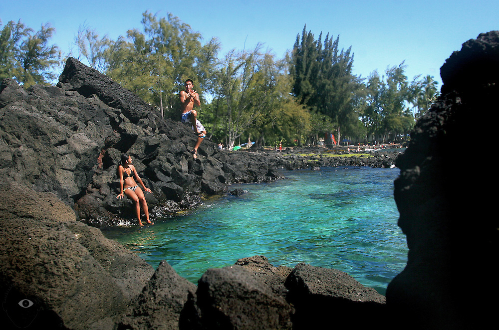 A high jump from the rocks is observed by his friend in a cove along the ocean at the Richardson Beach Park in Hilo on the Big Island of Hawaii.