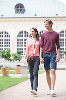 Young couple walking against buildings