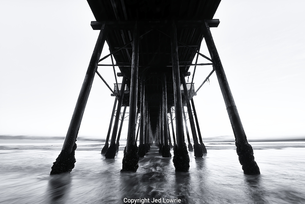 The sun setting behind the pier projected a light directly through the long tunnel created by the stilts. The structure of the pier draws your eye directly to the light.