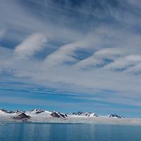 Lillehookbreen Glacier with wispy clouds overhead in the Lillehookfjorden Svalbard.