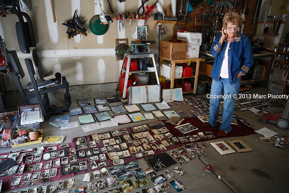 LONGMONT, CO - SEPTEMBER 16: Mary Ellen Briscoe, 81, of Longmont, Colorado pauses in her garage as she looks over historic family photos as residents clean up in the wake of a week of heavy flooding on September 16, 2013. Brisoce was trying to dry out and save family memories that were flooded in her basement. (Photo by Marc Piscotty/ © 2013)