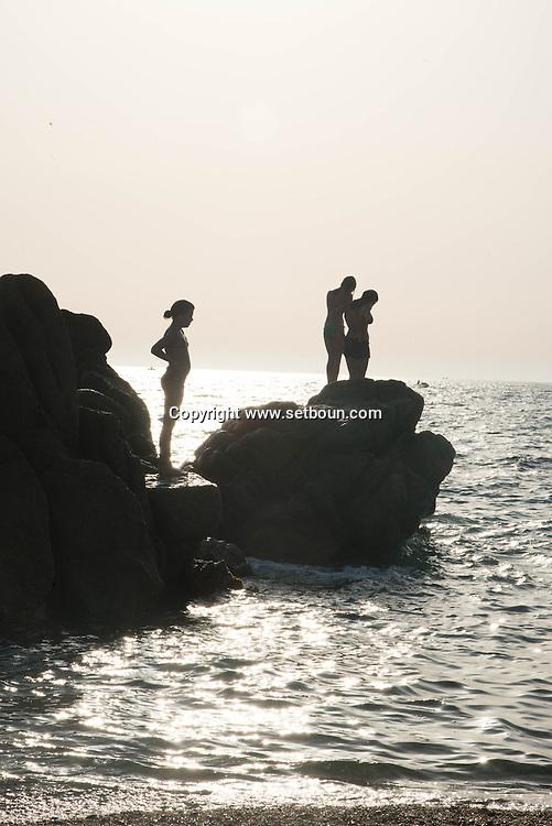 Corsica, Propriano area, Arena Bianca beach. young people and children diving in the mediterranean sea at sunset,/ des jeunes plongent dans la mer au coucher du soleil en Corse