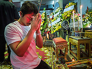 20 AUGUST 2015  - BANGKOK, THAILAND:  A man prays at the funeral for Yutnarong Singraw Thursday. More than 100 people gathered at Wat Bang Na Nok in Bangkok for the third day of the funeral rites for  Yutnarong Singraw, a Thai man who was killed in the bombing at the Erawan Shrine in Bangkok Monday. Yutnarong was delivering legal documents when the blast occurred. More than 20 people were killed and more than 100 injured in the blast.     PHOTO BY JACK KURTZ