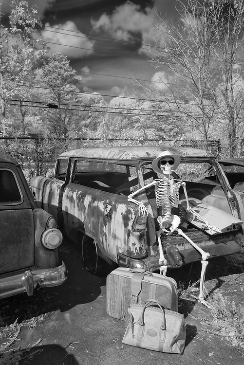 Out in the parking lot of the Highway to Hell Cafe after a filling breakfast, Jake waits with his bags for the bus heading for the town of Afterlife. He's looking forward to retirement and some final rest after working himself to the bone all those years in the Haunted House carnival attraction. This snazzy traveler wearing Ray Bans is perched on a 1956 Chevy station wagon that gave up the ghost a long time ago, with a 1955 Ford next door. What's a bony body to do while waiting? Smoke a cigar and work on the tan, of course!