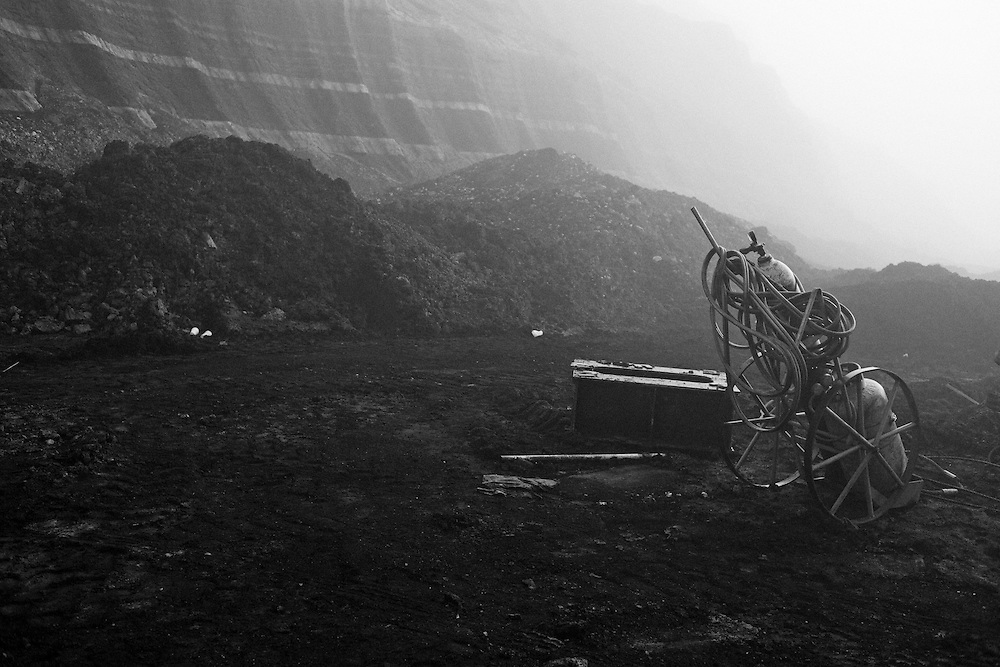 A foggy day at the south mine field. Coal mines and power stations in Ptolemaida, a city located north of Kozani, in west Macedonia, northern Greece...Dust and coal; ingredients that make up a very unhealthy environment. The city of Ptolemaida located in northern Greece, is known for its lignite mines which cover an area of 170,000 square meters. In the last twenty years, many villages were led to forced relocation because they were found at the heart of the mine which is growing and swallows many streets and fields...Greece is the second country of Europe in lignite production and sixth in the world. An irony for a country where the sun shines the most days of the year and the wind blows generously. People in the villages around the area suffer from untimely deaths and those who have the ability abandon the area for clear air and better life quality. Children are diagnosed with serious diseases of the respiratory system like bronchitis, rhinitis and asthma in their early years. The requests of the civilians for closing the lignite mine and the power station are vein. Unemployment in the region reaches 18%, aquifer has dropped from 50 to 500 meters and soon their land will be unsuitable for agriculture. The fines that the electric company pays from time to time for exceeding the pollution limits certainly do not solve the problem.