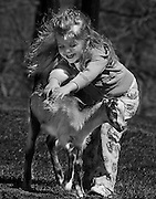 Photo by Phil Grout<br /> <br /> Three-year old Jordanna Gasparini of Monkton throws herself<br /> into Ag Day at Hereford High School and gives a three-week old<br /> &quot;La Mancha&quot; kid goat a two-handed pet with lots of laughter too.<br /> Jordanna and her family were on hand for the third annual Future<br /> Farmers of America Ag Day.