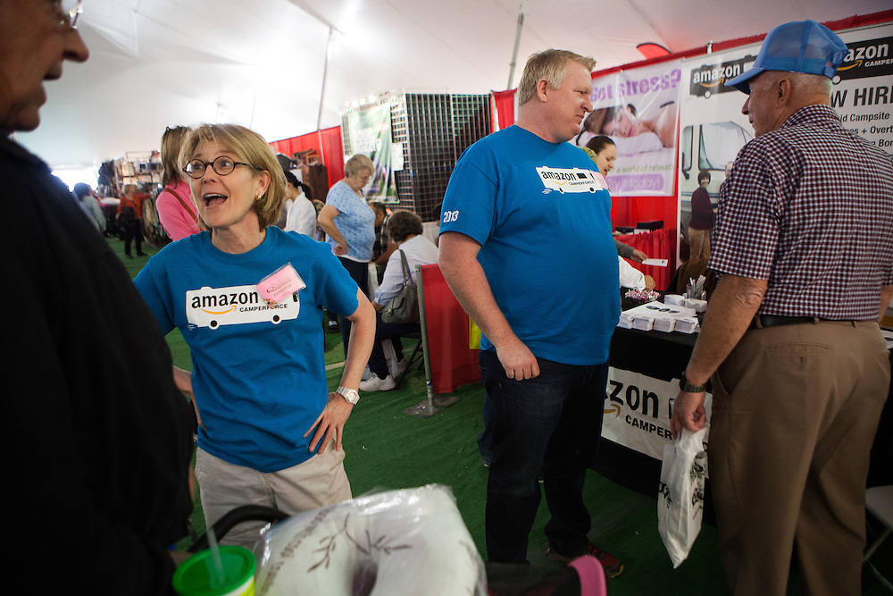 Amazon Camperforce recruiters Nancy Drotts, left, and Tom Stiltner, right, recruit workampers to work at Amazon distribution centers during the holidays at an RV show in Quartzite, Arizona.