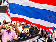 "02 JUNE 2013 - BANGKOK, THAILAND: Anti-government protesters march through Bangkok waving a Thai flag. The so called White Mask protesters are strong supporters of the Thai monarchy. About 300 people wearing the Guy Fawkes mask popularized by the movie ""V for Vendetta"" and Anonymous, the hackers' group, marched through central Bangkok Sunday demanding the resignation of Prime Minister Yingluck Shinawatra. They claim that Yingluck is acting as a puppet for her brother, former Prime Minister Thaksin Shinawatra, who was deposed by a military coup in 2006 and now lives in exile in Dubai.     PHOTO BY JACK KURTZ"