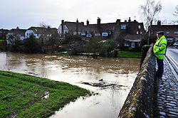 © Licensed to London News Pictures. 04/01/2016<br /> Kent flooding alert (04.01.2016) <br /> Local residents on the bridge,High Street,Yalding watching the river Beult.<br /> The river Beult in Yaldiing, Kent is very high this afternoon. <br />  A dozen areas of Kent has been put on flood alert by The Environment Agency.  This includes river Medway,Beult and Teise.<br /> <br /> (Byline:Grant Falvey/LNP)