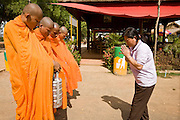 "26 JUNE 2006 - CENTRAL CAMBODIA: A woman gives ""alms"" to a group of Buddhist monks during a stop on Highway 6 between Phnom Penh and Siem Reap, Cambodia. PHOTO BY JACK KURTZ"