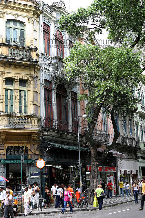 A view of the streets in the Centro district of Rio de Janeiro. The area is marked by an eclectic mix of Art Nouveau buildings fading in their grandeur, modern sky scrappers, and the odd colonial era structure. It is a network of narrow streets full of shops and businesses.