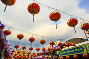 "09 FEBRUARY 2013 - BANGKOK, THAILAND: New Year's lanterns hang over the courtyard at Wat Mangkon Kamalawat, the largest Chinese temple in Chinatown in Bangkok. Bangkok has a large Chinese emigrant population, most of whom settled in Thailand in the 18th and 19th centuries. Chinese, or Lunar, New Year is celebrated with fireworks and parades in Chinese communities throughout Thailand. The coming year will be the ""Year of the Snake"" in the Chinese zodiac.    PHOTO BY JACK KURTZ"