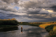 Barbara Nelson ties on a new fly while fishing for trout as an evening storm passes on the Teton River near the town of Driggs in the Teton Valley of southeast Idaho.
